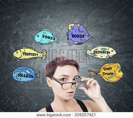 Portrait of a young surprised woman with short red hair taking off her glasses. She is standing near a blackboard with colorful fish with stock market words on them
