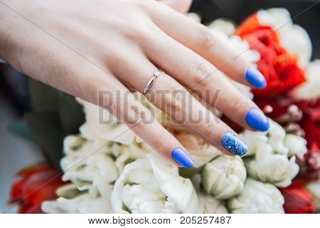 brides hand with wedding ring holding red and white coloured wedding bouquet close-up