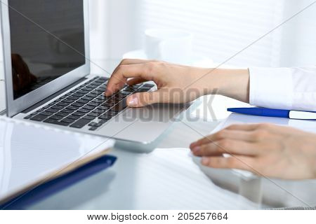 Close up of business woman hands typing on laptop computer.