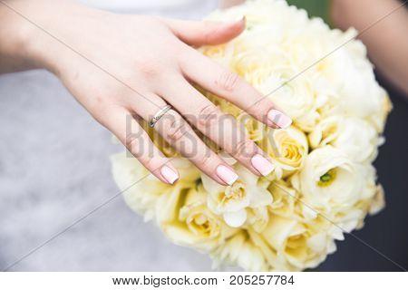 brides hand holding white coloured wedding bouquet close-up