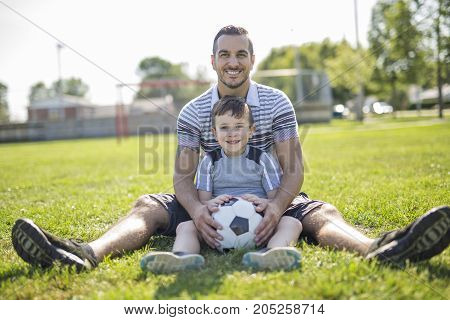 A man with child playing football outside on field
