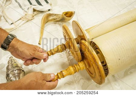 Hands holding the Torah scrolls with