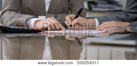 Group of business people and lawyers discussing contract while sitting at the table. Woman chief is taking pen for signing papers. Close-up of human hands at work. Meeting or negotiation concept in financial field og industry.