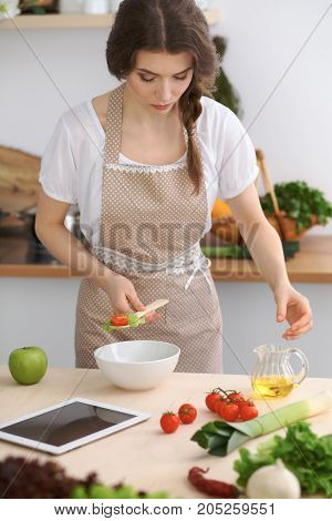 Young brunette woman is cooking and tasting fresh salad in the kitchen. Housewife holding wooden spoon in her hand. Food and health concept