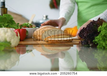 Closeup of human hands cooking in kitchen on the glass table with reflection. Housewife slicing bread.