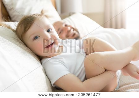 A Father with adorable baby toddler on bed