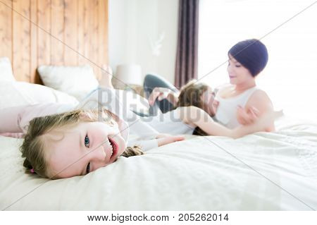 A Mother and two children in the bedroom on the bed