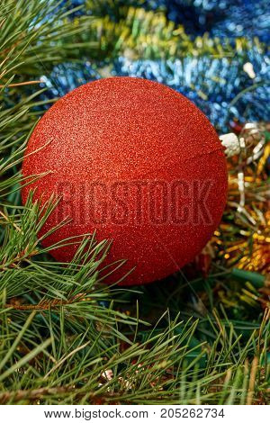 A large bright red ball lies on the New Year's colored ornaments