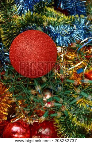 New Year`s ball in bright decorations and green needles