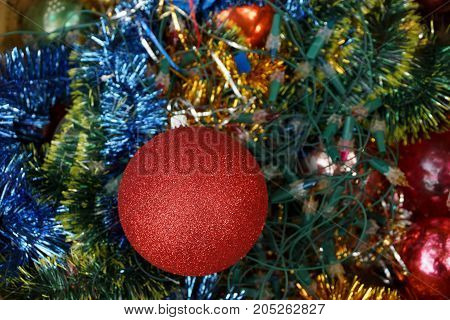 New Year's ball in bright decorations and green needles