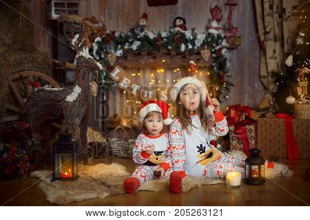 Happy little sisters in pajamas playing near a fireplace at Christmas Eve