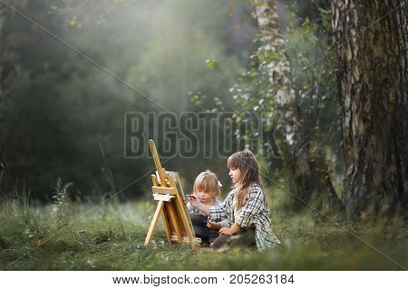 Little sisters painting at easel in autumn park
