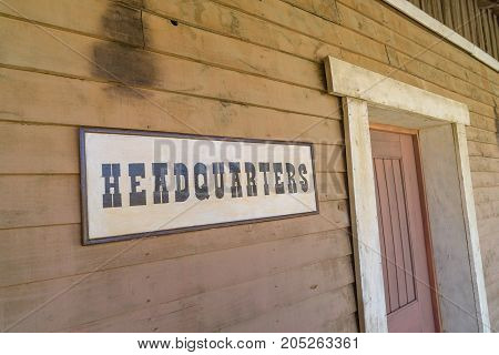 Background headquarters. Sign on wall with text headquarters and a door in western style.