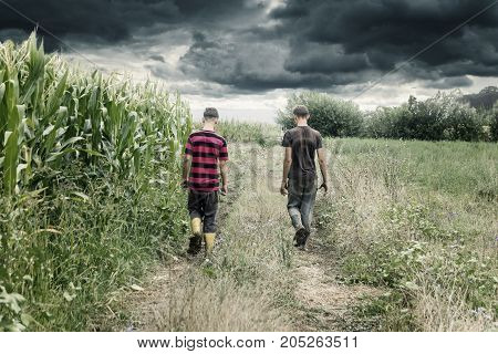 two farmer walking on tractor trail at agricultural field