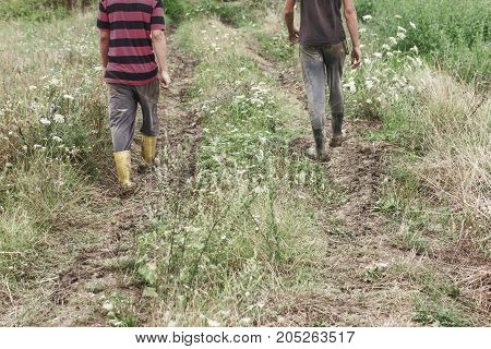 two farmer walking on tractor trail at green bloomy field
