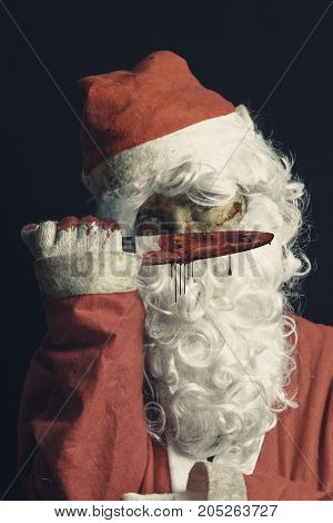 Horror Santa Claus shows his bloody knife