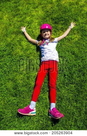 Young Girl resting on green grass after bike ride. Top view.