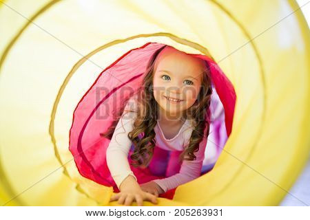 A Happy child girl plays indoor in a tunnel