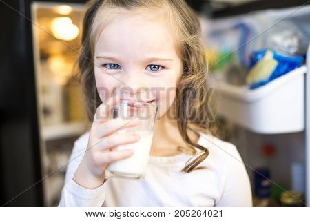 A Young white girl drinking fresh milk from a glass while standing in front of open refrigerator.