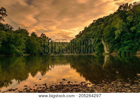 Meramec River, Onondaga Missouri State Park, landscape during the golden hour, sunset. Giving a yellow shine to clouds and reflection on water. A relaxing scene of peace and rest and a feeling of needing a fishing pole, a suit so you can swim or just a ch