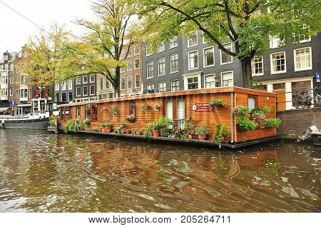Amsterdam Netherlands,October 14th 2010.The Tulip museum boat sits on a canal in Amsterdam with hotels and shops  in the background.Come to Amsterdam and enjoy the Dutch culture.