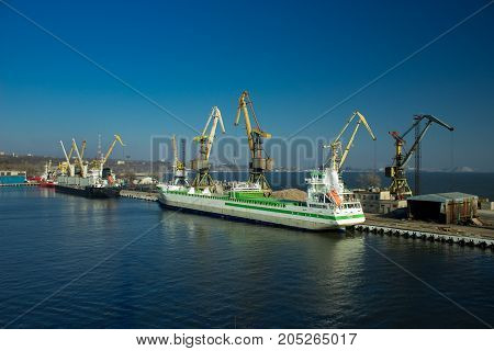 Cargo cranes transship bulk in the dock of Industrial Port