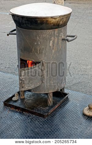 A boiler with a burning furnace and a closed pot in the street in the courtyard