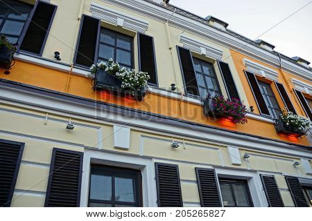 The wall of the house with windows with shutters and flower pots