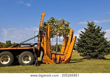 The mounted spade, jaws, and bucket are part of a tree removal machine  which removes and transplant young trees with their root system.