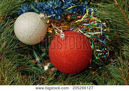two New Year's balls among ornaments and needles