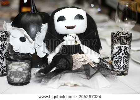 witch doll on halloween decorates a black table with a pumpkin and glasses