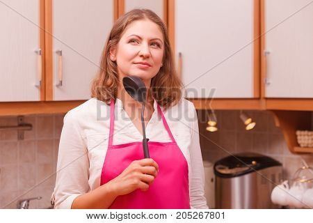 Housewife With Ladle In Kitchen