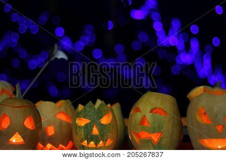 a lot of pumpkins with eyes and candles on halloween with blue background bokeh