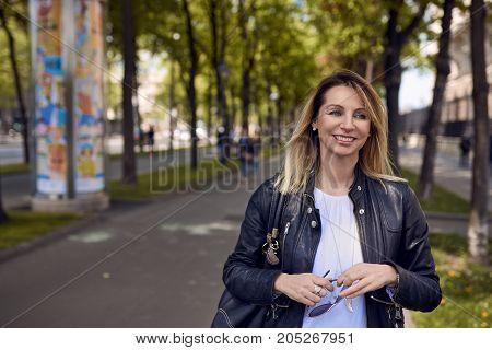 Smiling Woman Walking Along Sidewalk