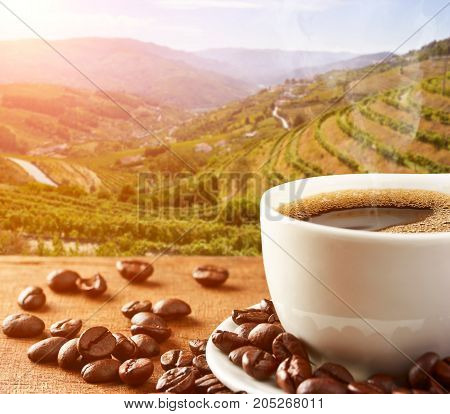 Hot Coffee cup with Coffee beans on the wooden table and Coffee plantations on background