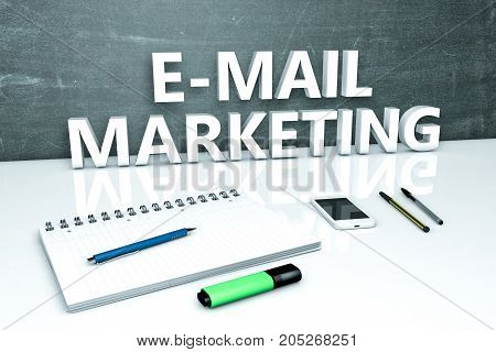 E-Mail Marketing - text concept with chalkboard, notebook, pens and mobile phone.