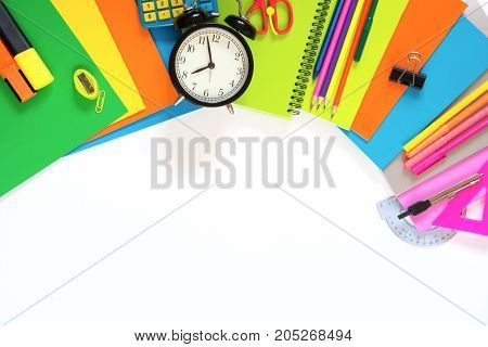 Colorful school supplies, book, and alarm clock on white background. Top view, flat lay. Top view, copy space.