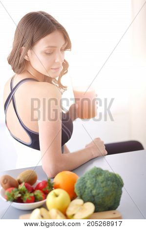 Girl sitting in the kitchen on the desk with fruit and glasses with juice