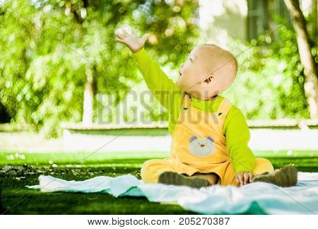 a baby sits on the mat in the park stretching a hand