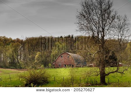Taken in southern Michigan rural landscape of old vintage farm barn. Rolling hills, green grass in the fields with trees in background. Rural view showing life of rural america.