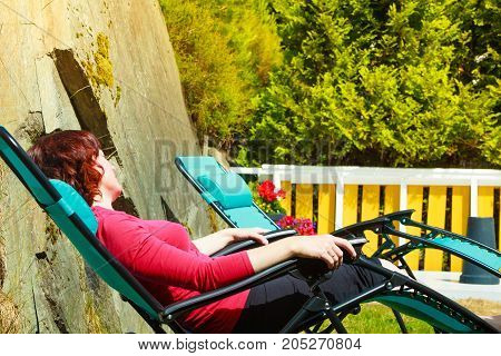 Adult Woman Relaxing On Sunbed In Garden