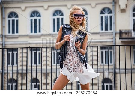Beautiful blond girl in stylish clothes posing outdoors in the city
