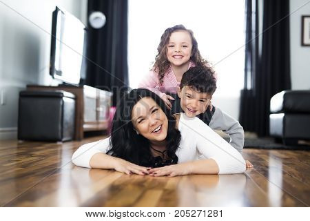 A Portrait of mother with her two children at home