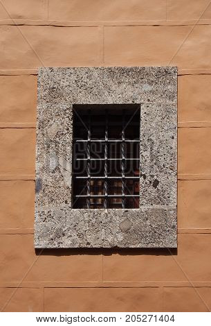 concrete window frame with thick security metal bars in a yellow painted stone wall