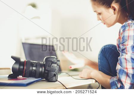 Female photographer sitting on the desk with laptop . Female photographer.