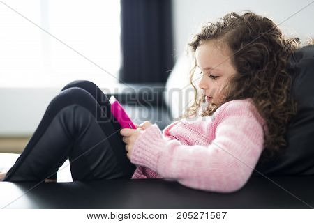 A Cute girl lying on sofa with tablet computer