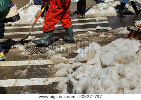 Business Man With Shovel Cleaning Snow Filled Street In Front Of The