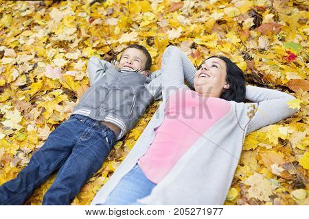 An Adorable little boy with his mother in autumn park