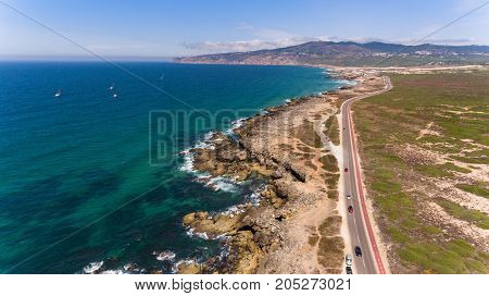 Beautiful road along the coast of ocean on sunny day, Portugal aerial view from