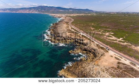 Beautiful road along the coast of ocean on sunny day, Portugal aerial view from Drone